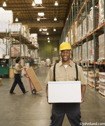 African american worker standing in a warehouse holding a large african american worker standing in a warehouse holding a large white cardboard box in his hands sciox Choice Image